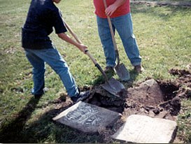 Fifth-grade students at North Cedar School in Mechanicsville help to reset a tombstone at historic Pioneer Grove Cemetery