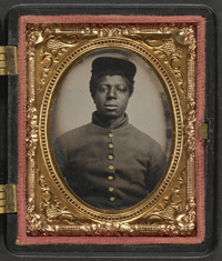 [Unidentified African American soldier in Union cavalry uniform with cavalry saber in front of painted backdrop showing landscape]