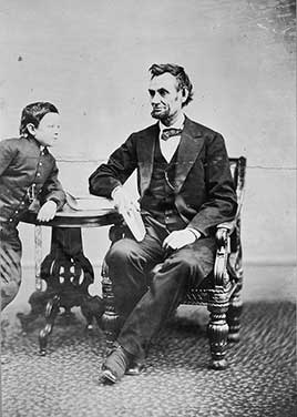 Abraham Lincoln, seated and holding a book, with his son Tad (Thomas) leaning on a table