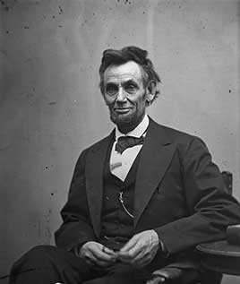 Abraham Lincoln, three-quarter length portrait, seated and holding his spectacles and a pencil