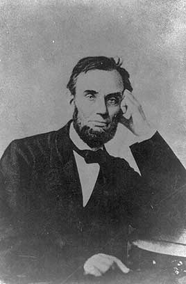 President Abraham Lincoln, seated, with his left hand on his face